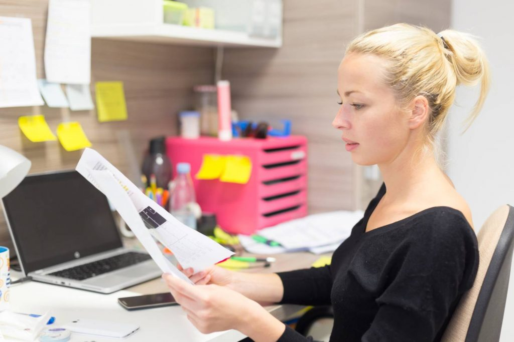 bookkeeper looking at tax paper