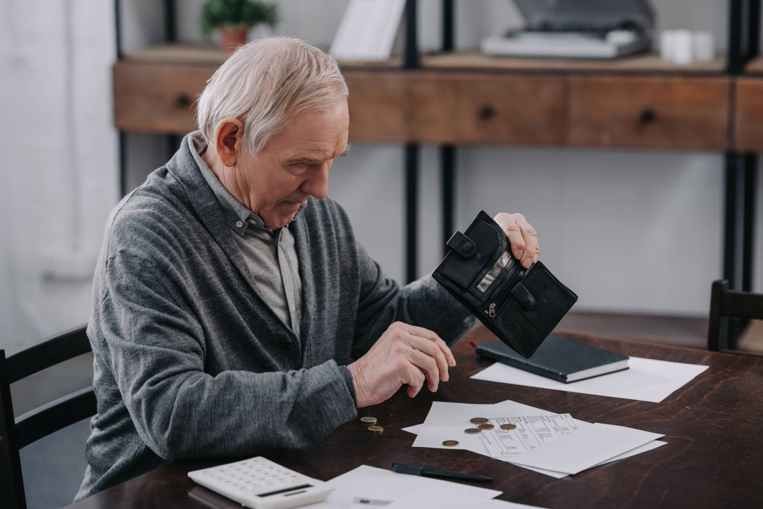 Male pensioner sitting at table with paperwork